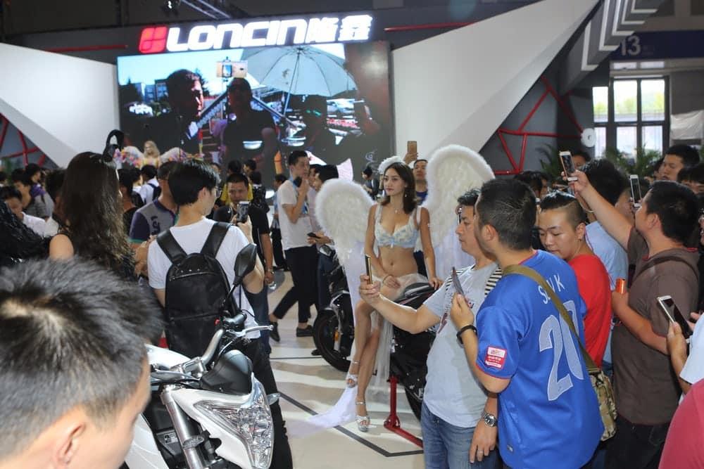 Lá, assim como aqui, em alguns estandes as modelos chamaram mais atenção do que as motos (Crédito: Mike Hanlon / New Atlas )